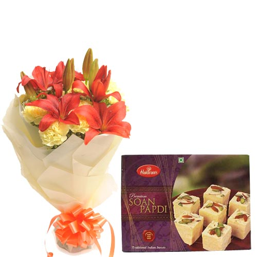 10 Yellow Carnations and 2 Orange Lillies wrapped in a colour paper with 500gms Soan papdi