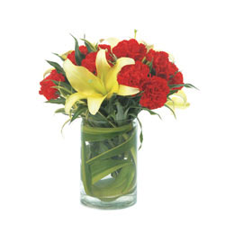 10 Red Carnations and 3 Yellow Lillies arranged in a desinger glass vase