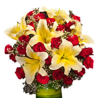 24 Red Roses and White Lillies arranged in a desinger glass vase